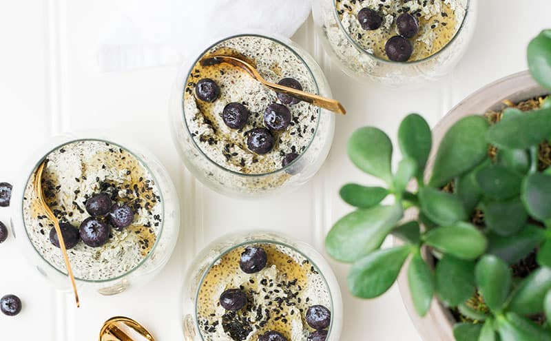 Juices in little glass bowls made from acai berries to get all its benefits, with pieces of blueberries and golden spoons on a white table.