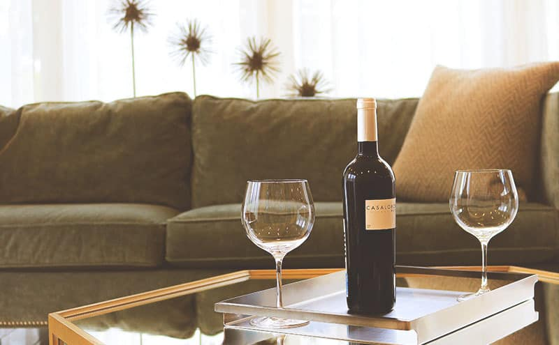 Two wine glasses and a glass of wine in a living room.
