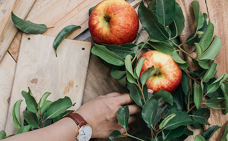 Two apples and multiple leaves from an apple thing on a light wooden boards and a hand with a watch on its wrist reaching for one of the apples.