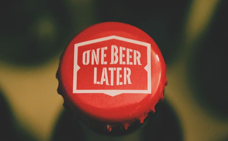 Close-up of a red bottlecap with the words 'one beer later' on it.