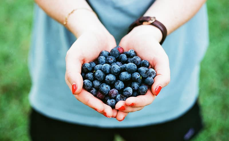 Woman holding blueberries in her palms outdoors.