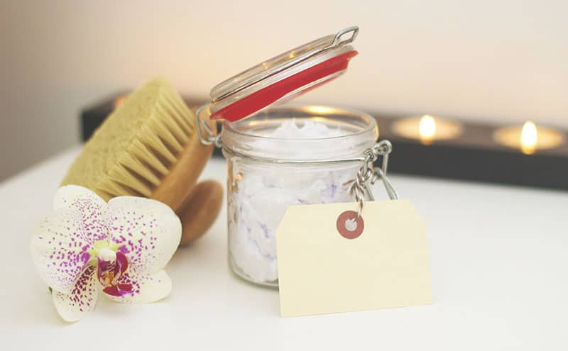 A flower, and a jar of cream for aftercare, next to a brush needed to achieve the benefits of dry skin brushing.