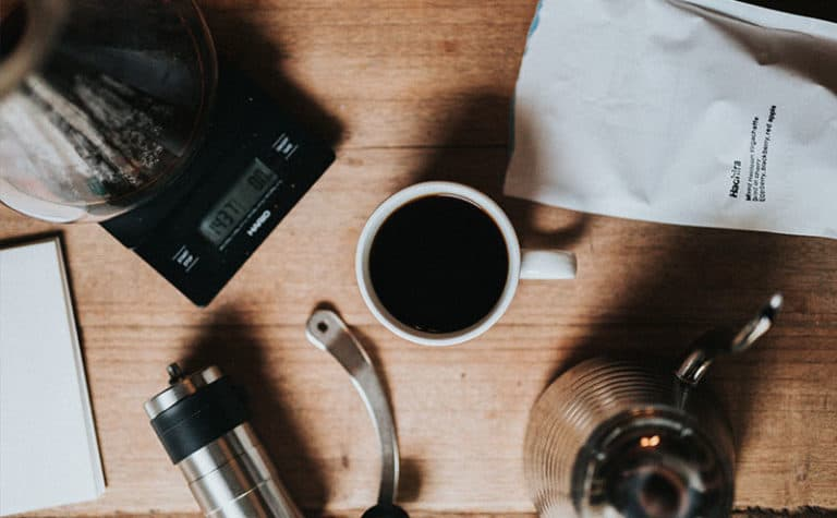 A cup of coffee next to a scale, a coffee grinder and a bag of coffee beans on wooden table.