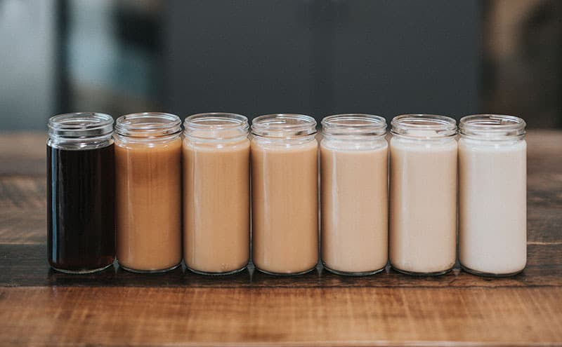 Seven different kinds of coffee in long, thin jars next to each other, from black coffee to milk.