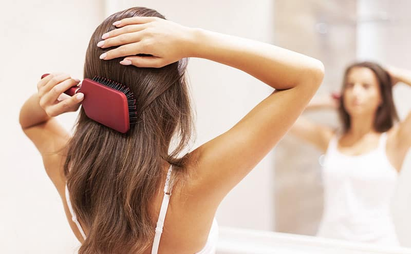 Woman brushing her hair in front of the mirror, wondering what causes dandruff.
