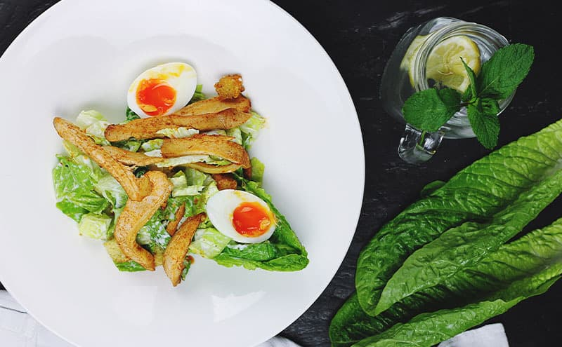 Chicken stripes with hard boiled eggs and salad on a white plate, surrounded by a mason jar of water with mint leaf and slice of lemon.