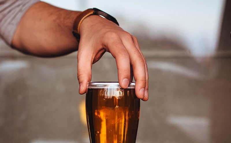Close up of a man's hand, with his fingers on a glass of beer.