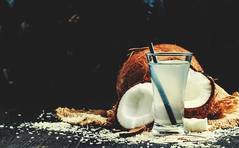A glass of coconut water with all its benefits, next to two halves of coconut and a whole coconut, outdoors.