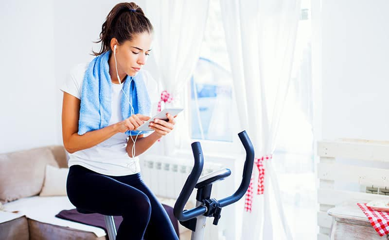 Woman reading on a tablet while sitting on the best folding exercise bike.