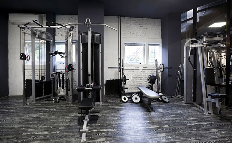 Exercise machines, weight benches, weights and pull-up bar in a home gym.