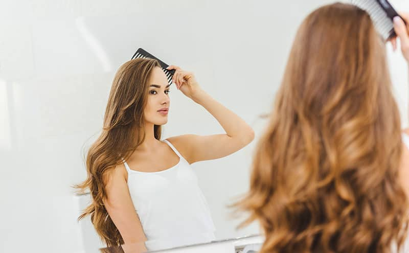 Woman brushing her hair at the mirror with one of the best dandruff brush.