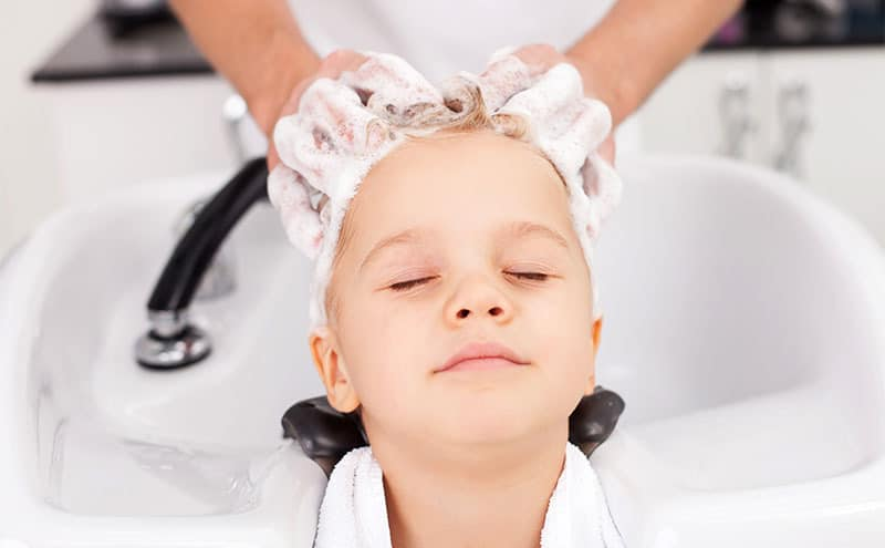 A professional is applying the best dandruff shampoo for kids on a boys hair.