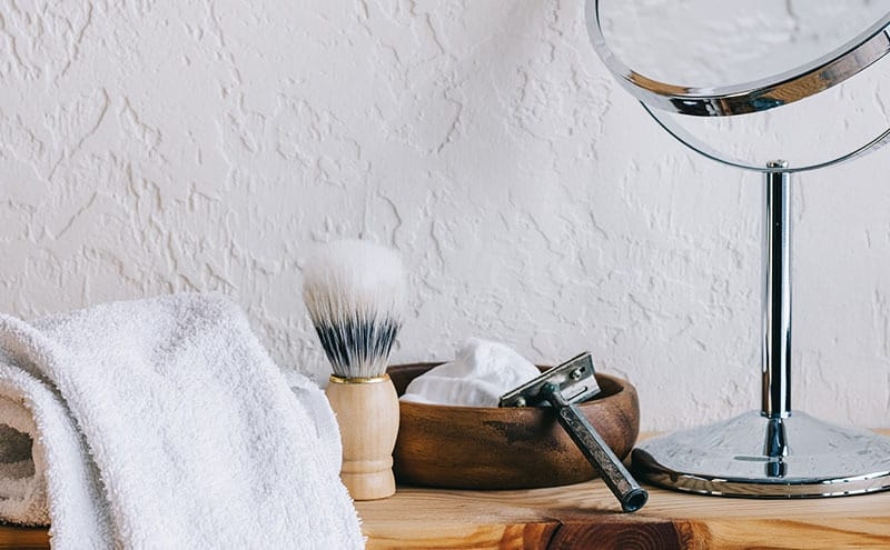A towel, a foam brush, foam in a wooden bowl, razor and a small mirror on a wooden counter.