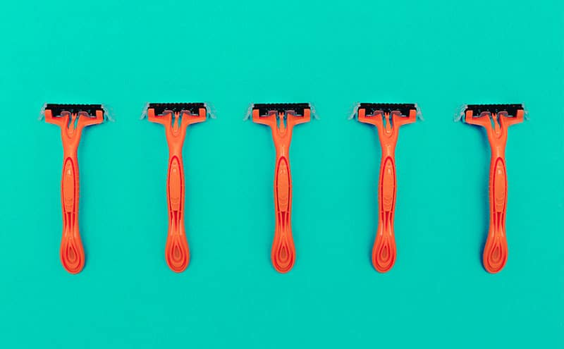 Five identical orange razors placed next to each other on blueish green background.