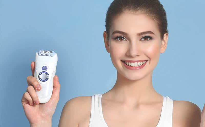 Woman smiling at us as she's showing off her best electric razor for women in front of light blue background.