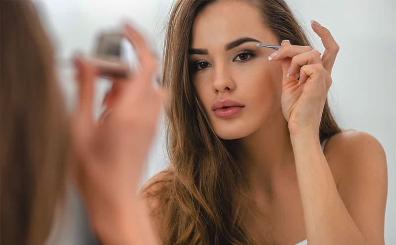 Close-up of woman using tweezers at the mirror to adjust her eyebrows.
