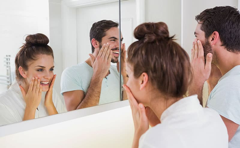 Couple looking at the mirror in the bathroom, smiling.