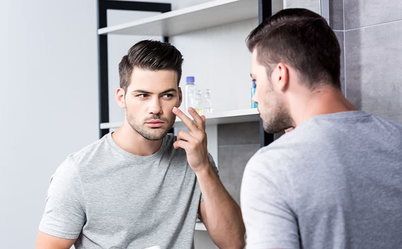 Man trying his best at the mirror to correctly apply hair removal cream for men.