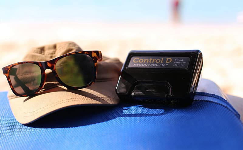A cap, sunglasses and a blood glucose monitor at what appears to be a beach, while woman is getting ready to check blood sugar, after consuming fructose.