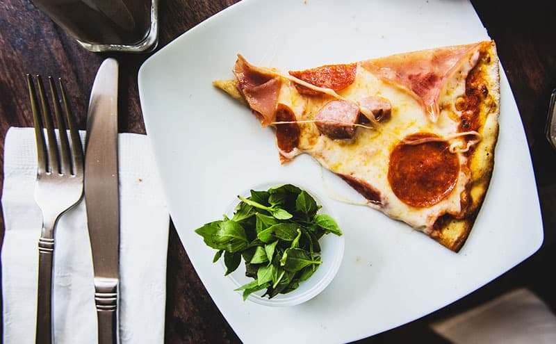 A slice of pizza on white plate with a small bowl of basil and cutlery next to it on wooden table.