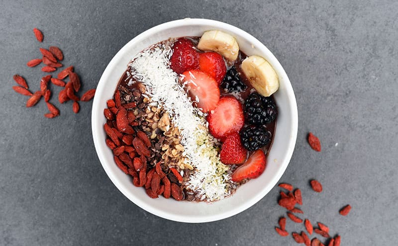A bowl of goji berries, with walnuts, strawberries, mulberries, banana and coconut on grey background