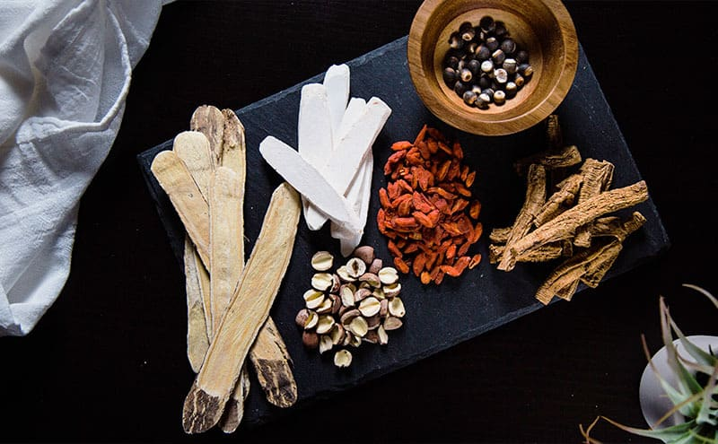 Goji berries and other nuts and spices on a dark plate.