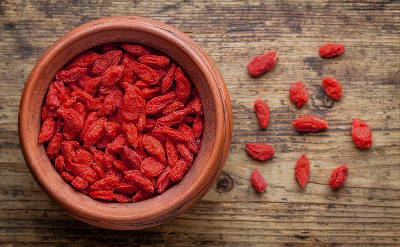 A wooden bowl of ripe goji berries with pieces of goji berries next to it on wooden table.
