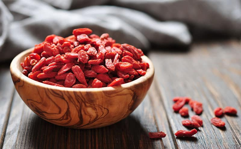 A wooden bowl full of goji berries with all its benefits and side effects.