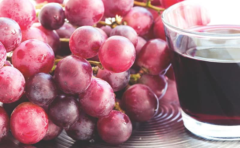 A small glass of grape juice next to grapes on a metal tray.
