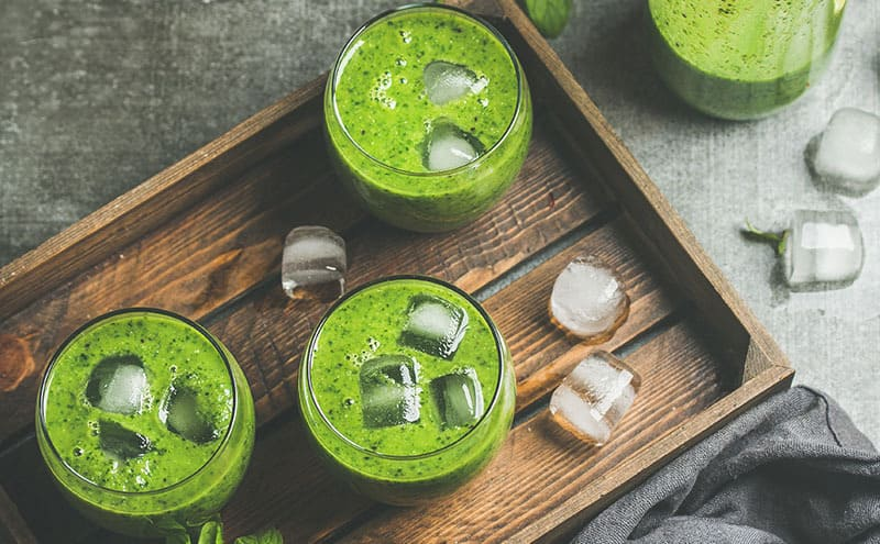 Three glasses of cilantro juice with ice on a wooden tray.