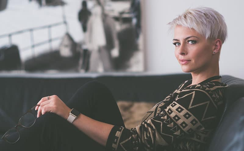 Woman with short grey hair sitting on a sofa while holding her reading glasses.