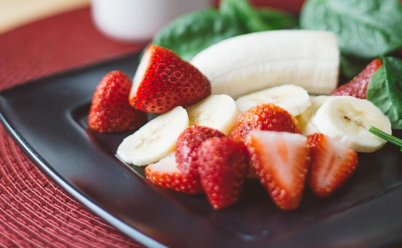 Strawberries, a half and sliced bananas, leaves on a dark square-shaped plate.