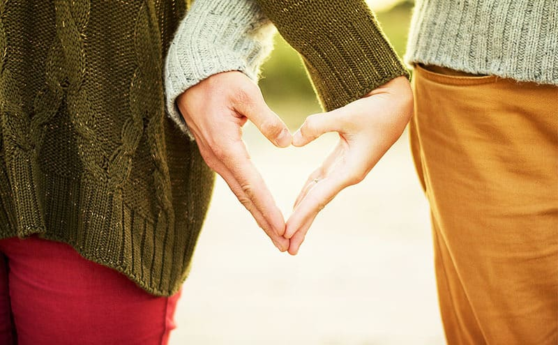 Woman and man in sweaters crossing their hands with each other, forming a heart shape with their palms.