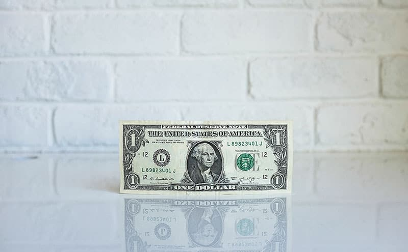 A one dollar bill standing on its side on a reflective white surface, in front of a white brick wall.
