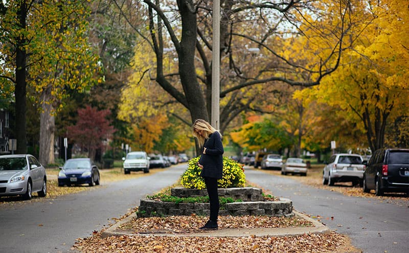 A pregnant woman standing on sidewalk between two car lanes, on autumn leaves, holding her belly looking down on it.