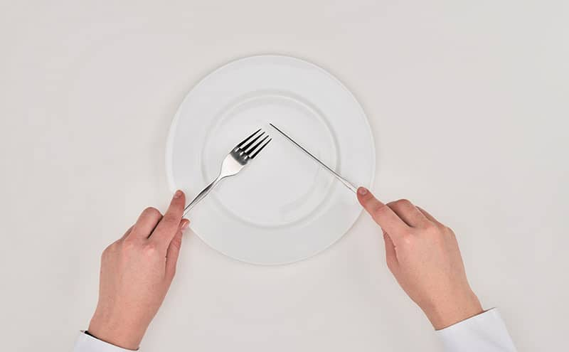 Man using forks and knives on a perfectly empty white plate.