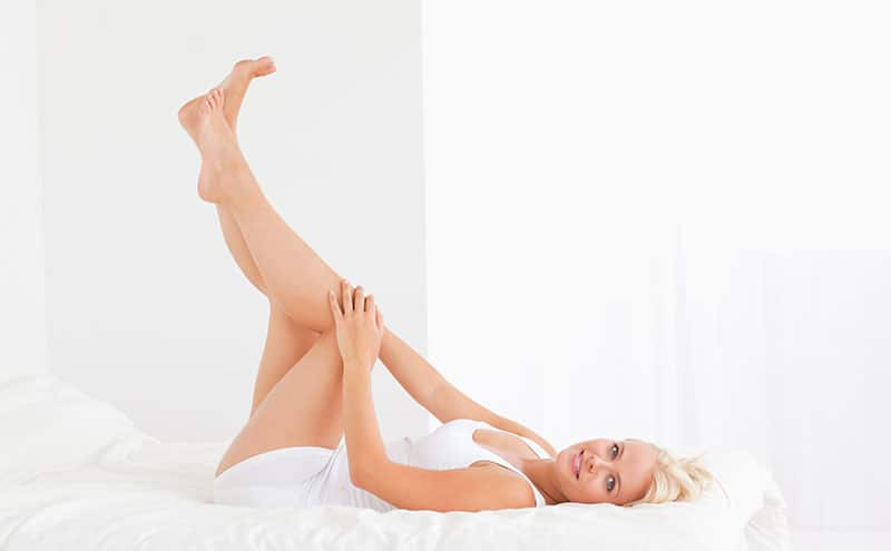Woman happy about having hairless legs, lifting her feet high on bed.