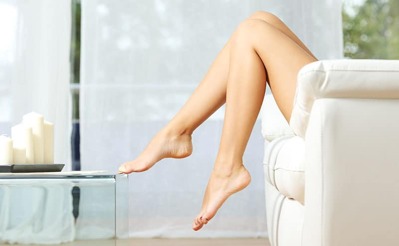 Woman with bare legs enjoying the aftermath of the best home laser hair removal.