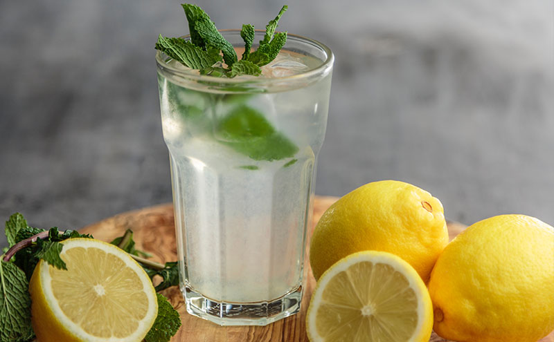 A glass of lemon water with ice cubes and leafs of mint, surrounded wit two full two half lemons on a small medium brown wooden table.