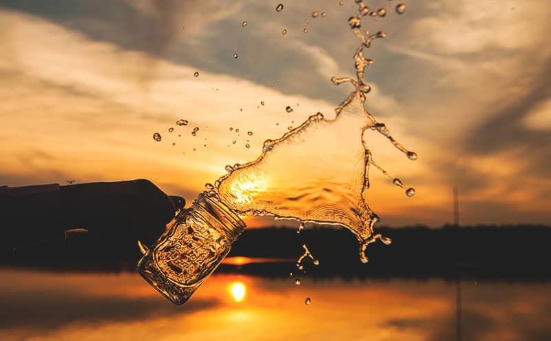 Water is being spilled out of a mason jar in front of the sunset.