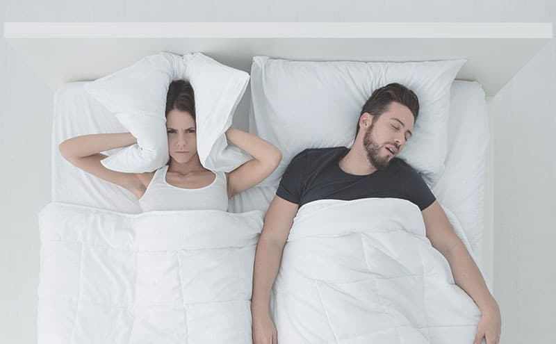 Woman covers her ears with her pillow because of her snoring husband in the bed.