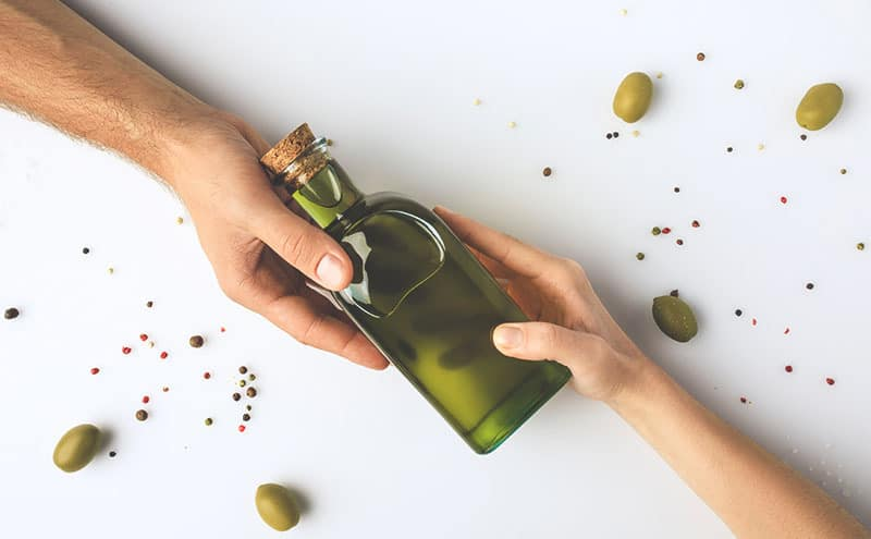 Two hand holding a bottle of olive oil from the opposite directions, surrounded with olives and spices.