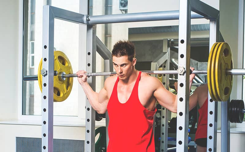 Man in red sleeveless shirt standing with a barbell at a power rack.