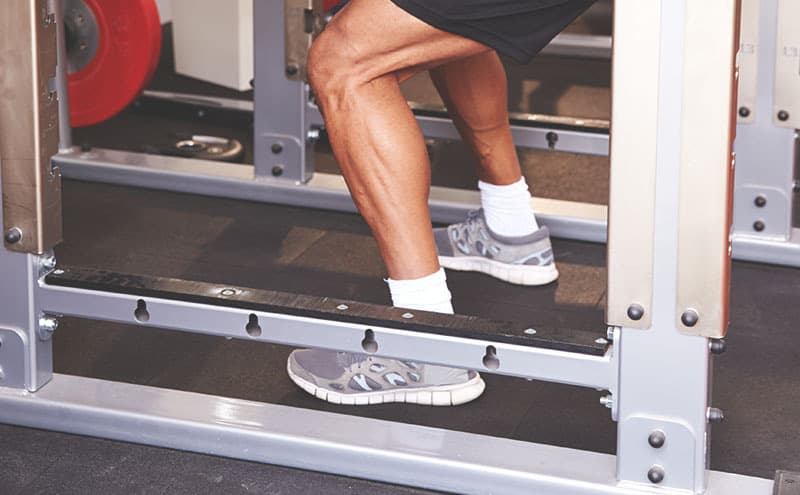 Close-up of man's legs as he's giving his best at a fitness power rack in his home gym.