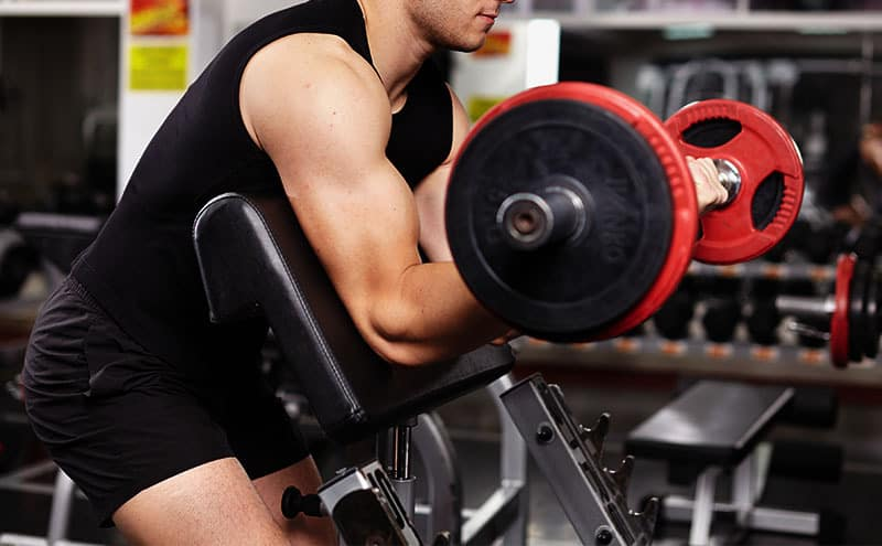 Man giving her best with a dumbbell on a preacher curl bench.