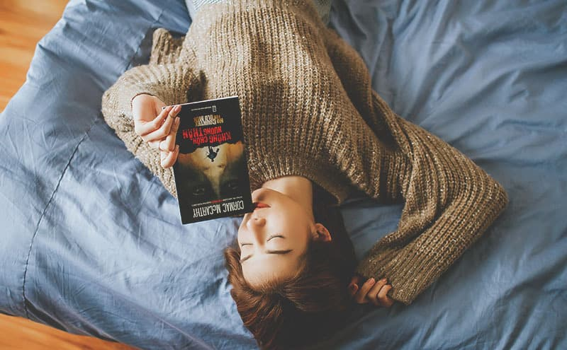 Woman in sweater laying on her back in her bed while holding a book.