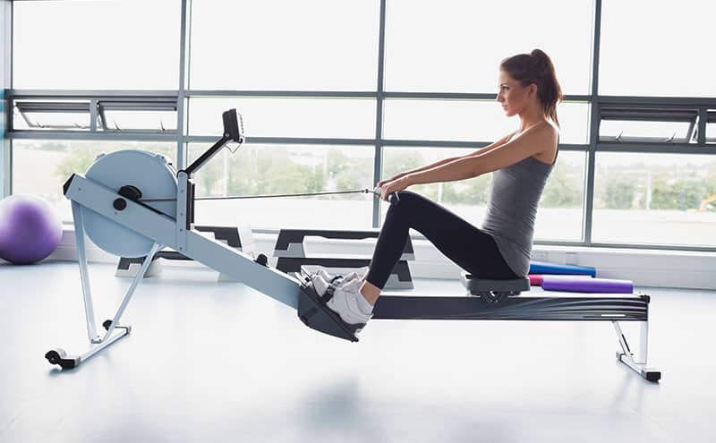 Woman at the gym trying her best on a magnetic rowing machine.