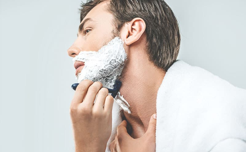 Man shaving his beard with the best safety razor for beginners.