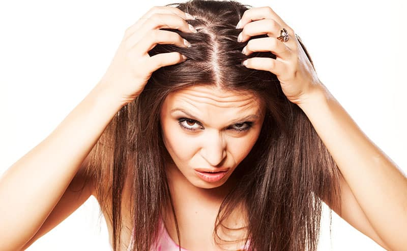 Woman looking at her hair, deciding she needs the best scalp eczema shampoo.