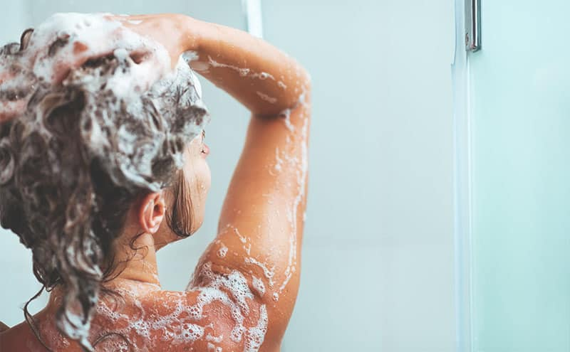 Woman in the shower washing her hair with the best shampoo for psoriasis.